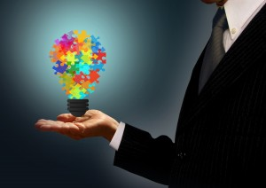 Businessman holding a jigsaw lightbulb - Ideas and creativity concept